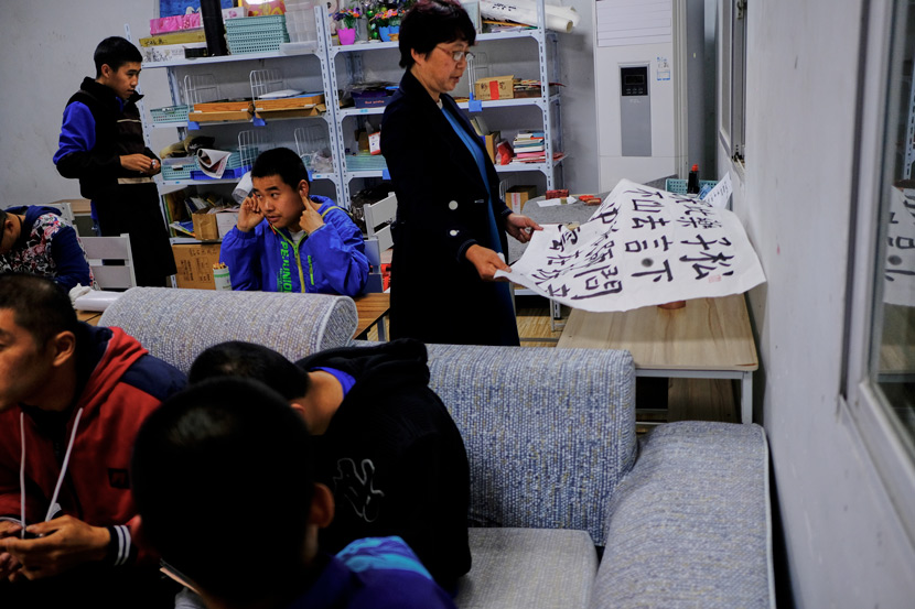 All of the residents and carers at Home of the Stars gather in a downstairs classroom to take part in evening activities, in Jinzhai County, Anhui province, March 2021. Yu (right) helps her son practice calligraphy. Wu Huiyuan/Sixth Tone