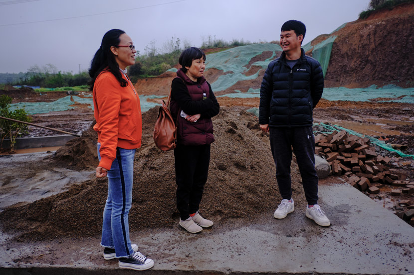 Tian Hanfen (left) and a staff member (right) accompany Shang Yao (center) to visit the construction site, in Jinzhai County, Anhui province, March 2021. It was Shang's first time visiting the site of her future home. Wu Huiyuan/Sixth Tone