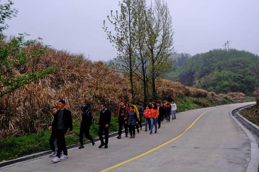The residents hike in single file along the mountain road, accompanied by the carers, in Jinzhai County, Anhui province, March 2021. Wu Huiyuan/Sixth Tone