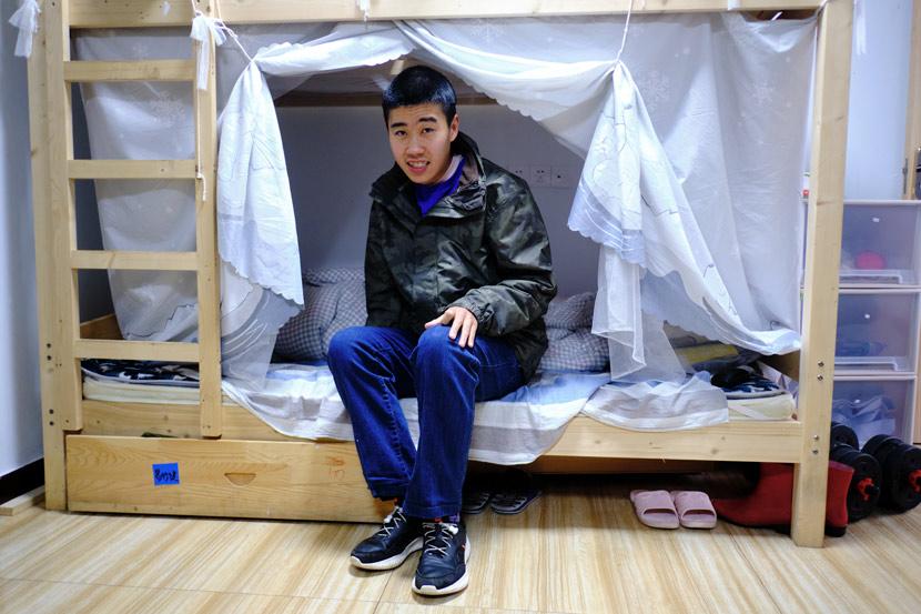 Yu Hua's son Yi Xingjian, 25, sits on his bed at Home of the Stars in Jinzhai County, Anhui province, March 2021. Wu Huiyuan/Sixth Tone