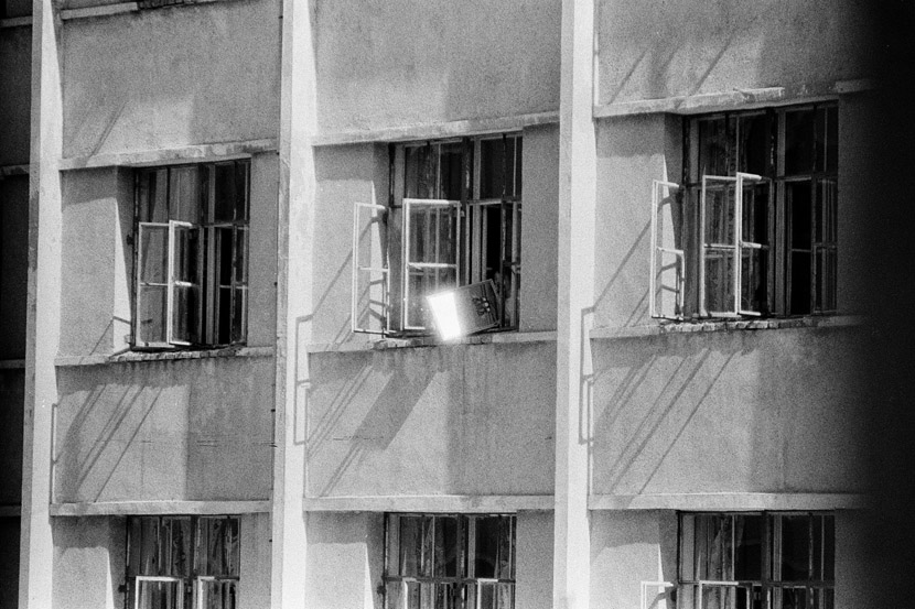 1995: A woman uses a mirror to reflect sunlight into the men's dormitory.