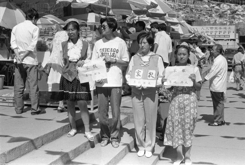 1994: Women from the Northeast Normal University looking for work as tutors in downtown Changchun. Those days, tutoring was the most common way for students to earn money. Most held up such cardboard signs at spots across the city hoping to land a gig.