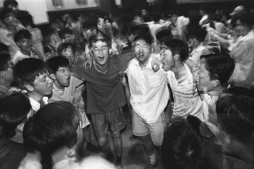 1996: Students singing together on the railway platform before saying goodbye.