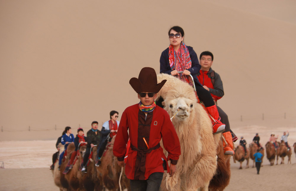 Tourists ride camels in Dunhuang, Gansu province, May 1, 2021. Zhang Xiaoliang/People Visual