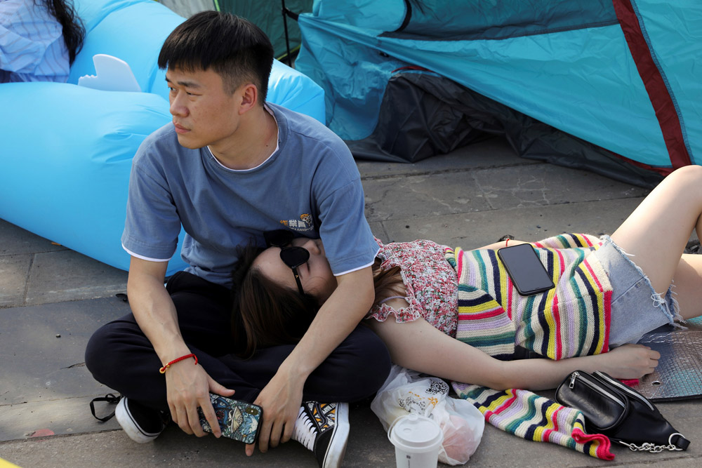 A couple takes a break during the Strawberry Music Festival in Wuhan, Hubei Province, May 1, 2021. Tingshu Wang/Reuters/IC