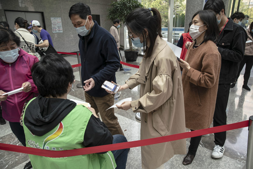A woman shows her registration code to a volunteer (in green) while standing in line at a COVID-19 vaccination center in Shanghai, April 3, 2021. Qilai Shen/Bloomberg/People Visual