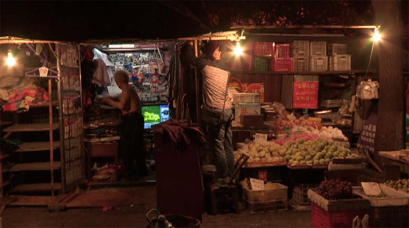 A screenshot from the film shows Wang Tiancheng (left) and his son at their street stall. Courtesy of Dai Nianwen