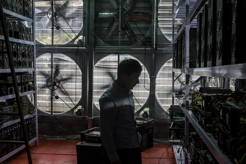 A manager stands near a wall of fans inside a bitcoin mine in rural Sichuan province, 2016. Liu Xingzhe/People Visual