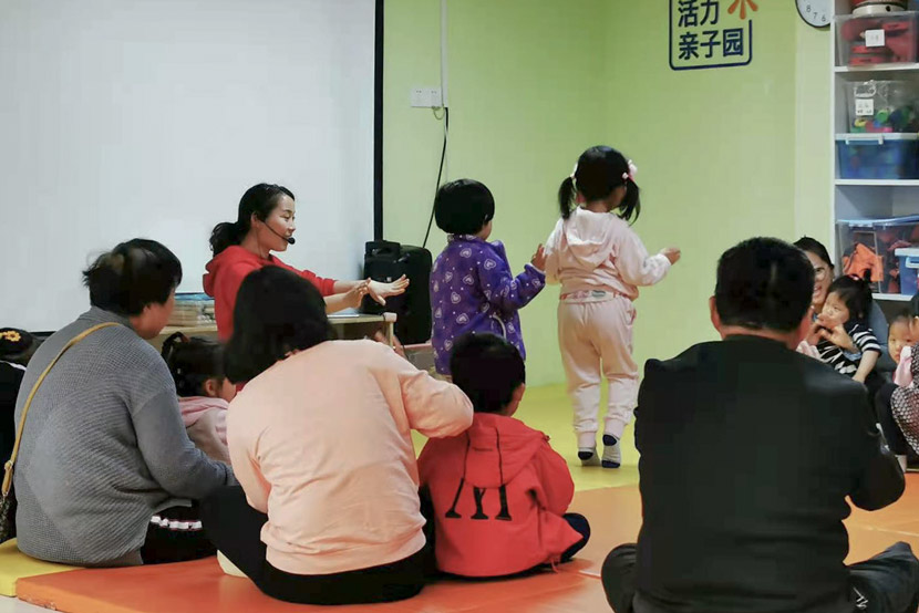 A teacher guides children and their family members at Vibrant Communities' center in Shanghai, April 2021. Cai Yiwen/Sixth Tone