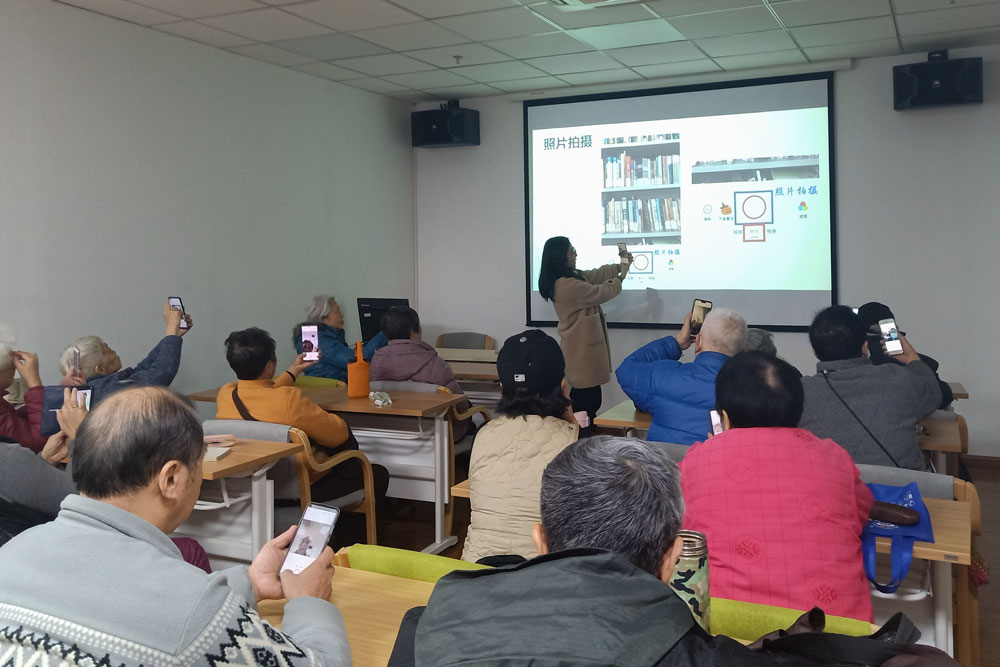 """A volunteer teaches the elderly how to take photos with their smartphones, in Shanghai, Jan. 6, 2021. Courtesy of Shanghai Normal University's """"Smart Elderly"""" program"""