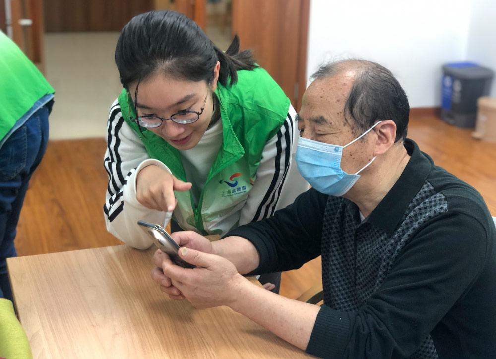 "Volunteer Cai Yijun teaches a senior how to use his phone, in Shanghai, November 2020. Courtesy of Shanghai Normal University's ""Smart Elderly"" program"
