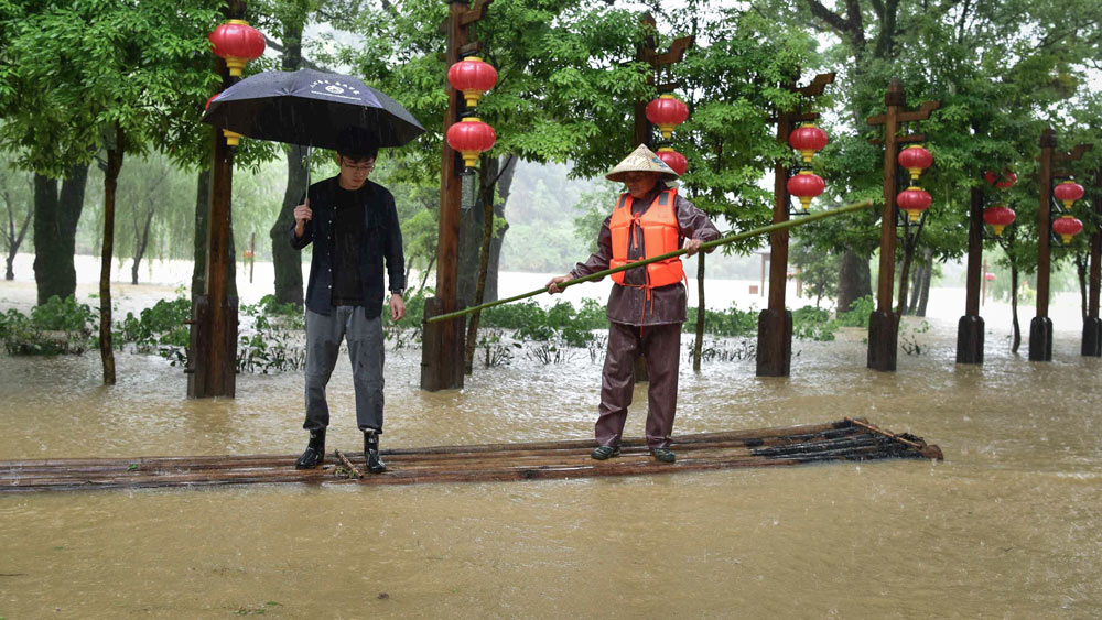 A rescue worker uses a bamboo raft to guide a resident to safety during a flood in Songxi County, Fujian province, May 22, 2021. Zhang Lijun/CNS/People Visual