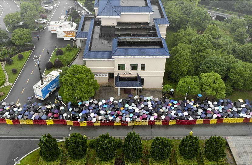 People with umbrellas wait in line in the rain to bid farewell to Yuan Longping outside the Mingyangshan Funeral Home, where his body lies, in Changsha, Hunan province, May 23, 2021. Yang Huafeng/CNS/People Visual