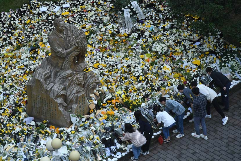 People leave flowers and other mementos at the statue of Yuan Longping on the campus of his alma mater, Southwest University, in Chongqing, May 23, 2021. People Visual