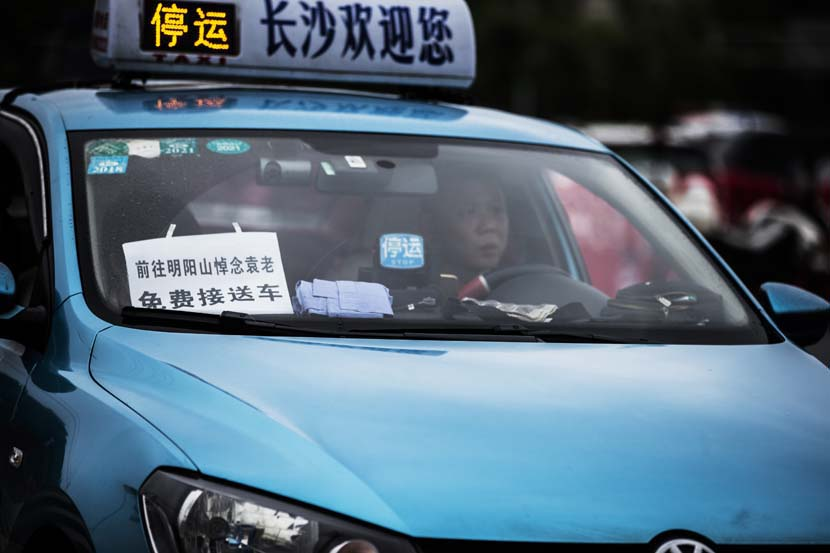 """A paper sign in a taxi's windshield reads """"Free ride for those going to bid farewell to Yuan Longping at the Mingyangshan Funeral Home,"""" Changsha, Hunan province, May 23, 2021. People Visual"""