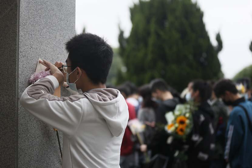 A man writes a note to Yuan Longping at the Mingyangshan Funeral Home in Changsha, Hunan province, May 23, 2021. People Visual
