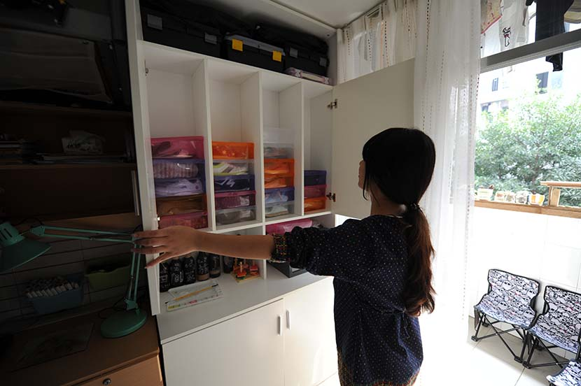 A girl opens a closet at her dormitory in Changsha, Hunan province, Oct. 23, 2015. People Visual