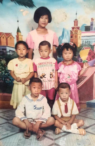 A family photo of Li Dongmei (back row), her third sister (second row, far left), and her cousins. The picture was taken shortly after her mother died. Courtesy of Li Dongmei