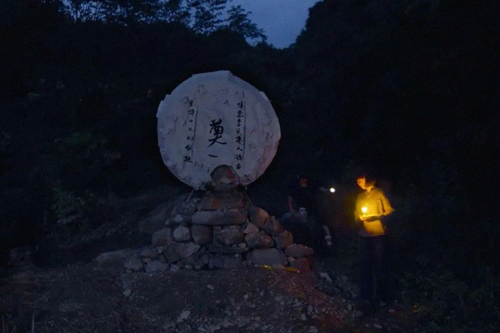 """A still from """"Mama"""" showing Xiaoxian and her younger sister lighting lamps for their deceased mother. Courtesy of Li Dongmei"""