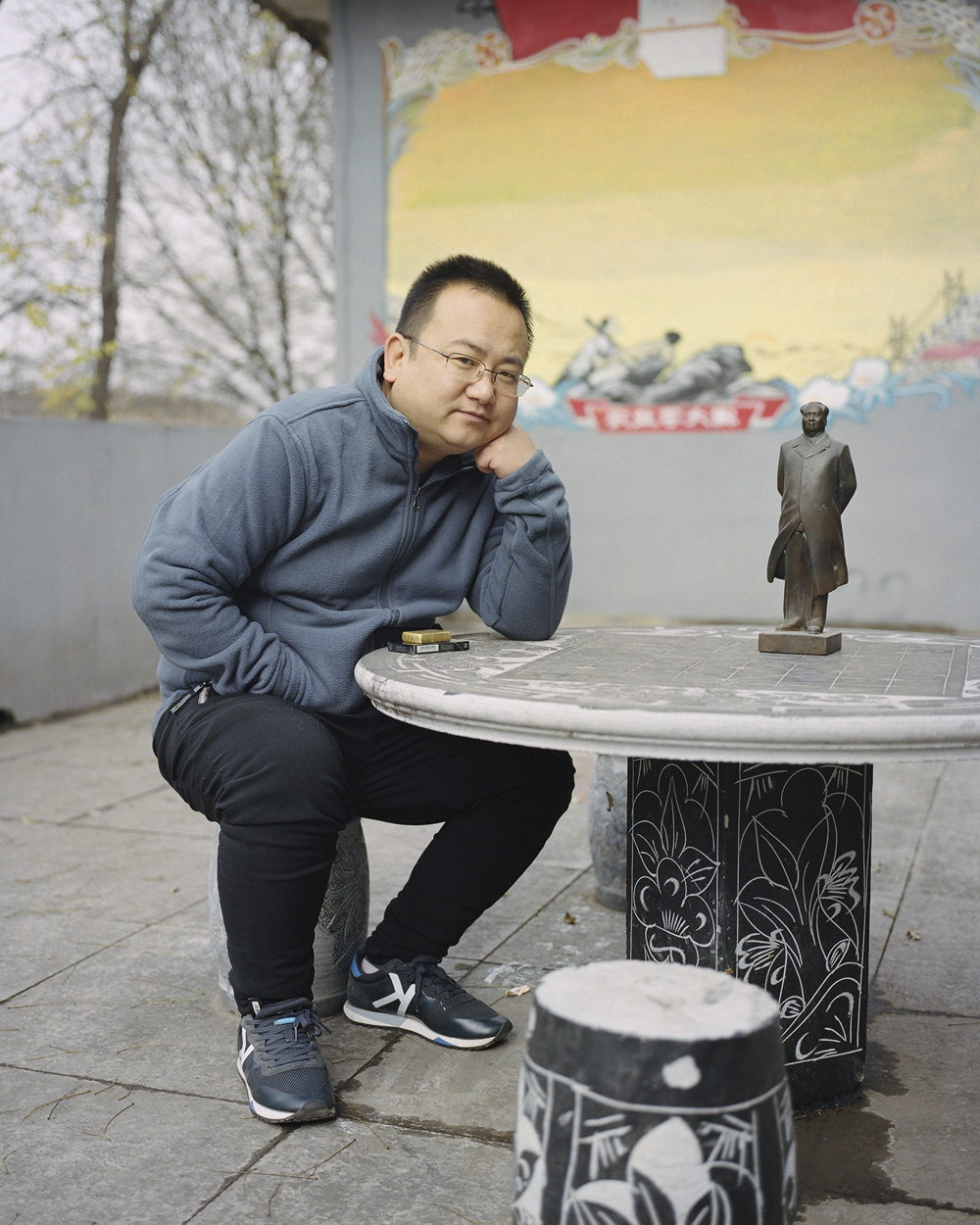 Zhao Mingxing poses for a photo with a Mao statue at his museum in Dazhai Village, Shanxi province, Nov. 17, 2018. Shi Yangkun/Sixth Tone