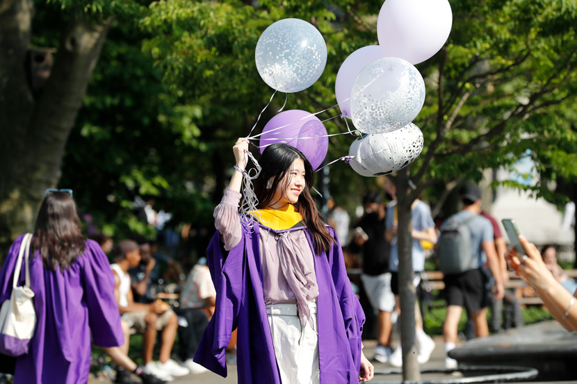 A graduate from New York University poses for a photo in New York, May 19, 2021. Liao Pan/CNS/People Visual