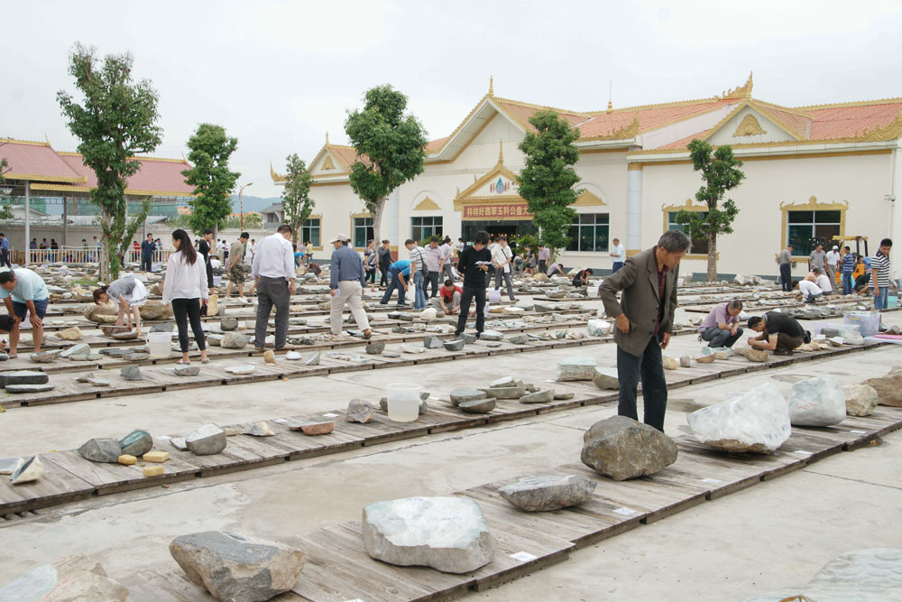 Buyers inspect stones for sale at an event in Ruili, Yunnan Province, 2011. Courtesy of Ruili Yangyanghao Jewelry Trade Auctioneering Co., Ltd.