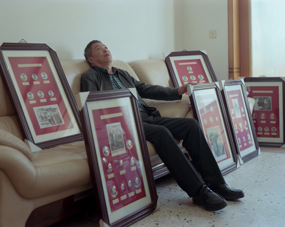 """Li Yanxiao sits with his collection of Chairman Mao badges from the """"learn from Dazhai in agriculture"""" campaign, in Dazhai Village, Shanxi province, April 19, 2021. Shi Yangkun/Sixth Tone"""