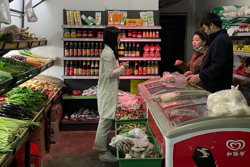 Zhang Yunhua (right) talks to a customer at her convenience store, in Wuhan, Hubei province, April 25, 2021. Wu Peiyue for Sixth Tone