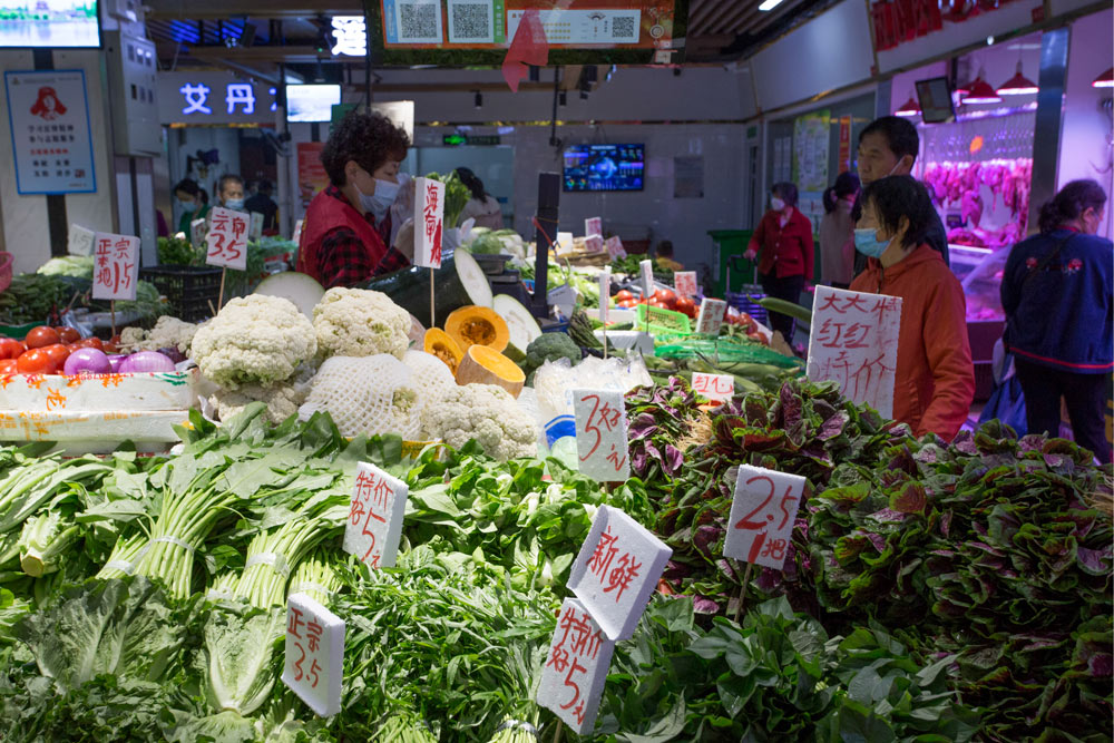 Liu Guilan (left) talks to a customer at her vegetable stall at a wet market, in Wuhan, Hubei province, April 25, 2021. Wu Peiyue for Sixth Tone