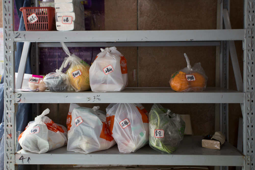 Groceries sit on a set of shelves, waiting to be collected by local residents, in Wuhan, Hubei province, April 25, 2021. Wu Peiyue for Sixth Tone