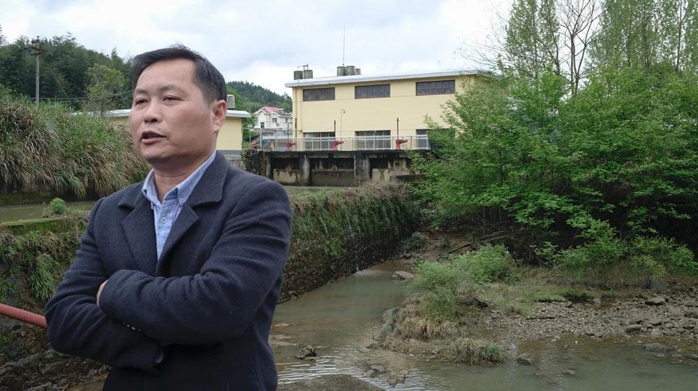 Chen Tai'an poses for a photo atop the Hongsha Hydropower Station dam in Liuyang, Hunan province, 2021. Diao Fanchao for Sixth Tone