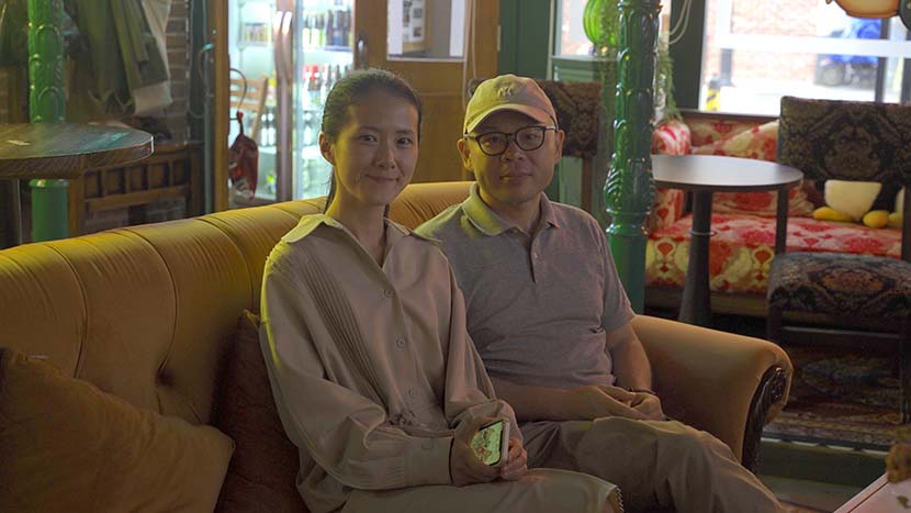 """Du Xin and his wife, """"Rachel,"""" pose for a photo at the Central Perk café, in Hangzhou, Zhejiang province, May 11, 2021. Xintian Wang for Sixth Tone"""