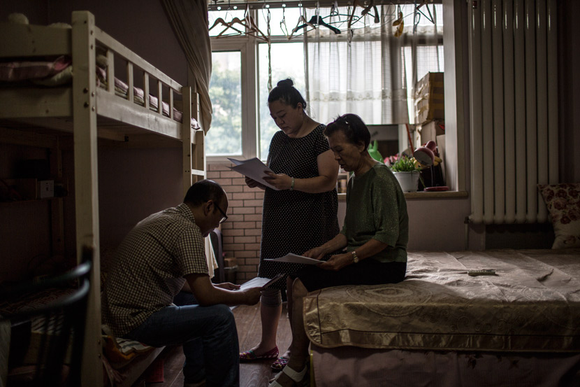 From right to left, Li Shuda, her daughter, and her son-in-law talk among themselves at a rental apartment in Beijing, July 12, 2017. Zhao Heting/Tencent News