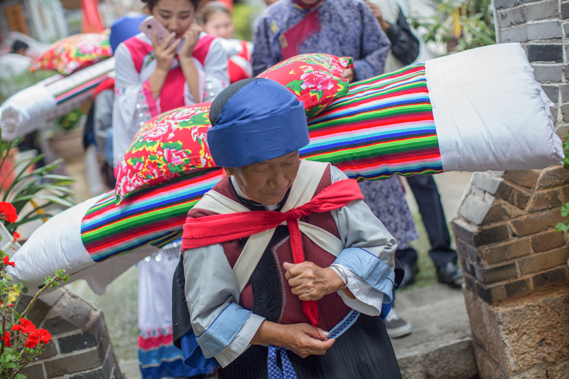 An old woman carries a quilt and pillow as part of the bridal procession during a traditional Naxi wedding ceremony in Lijiang, Yunnan province, Aug. 5, 2017. Daniel Holmes/Sixth Tone