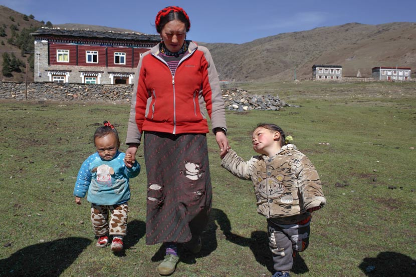 Wosar Lhamo takes her sons for a walk in Tagong Township, Kangding County, Sichuan province, May 9, 2017. Zhou Pinglang/Sixth Tone