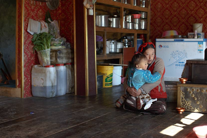 Wosar Lhamo holds her young son at home in Tagong Township, Kangding County, Sichuan province, May 9, 2017. Zhou Pinglang/Sixth Tone