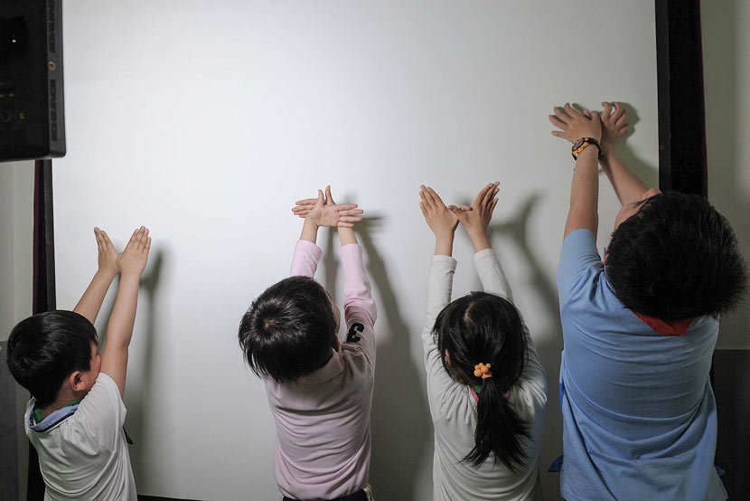 Students make shadows with their hands at an elementary school in Shanghai, May 22, 2014. Lai Xinlin for Sixth Tone