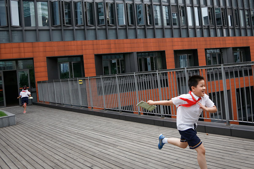 A student runs outside an elementary school building after class in Shanghai, Sept. 24, 2013. Lan Hui for Sixth Tone