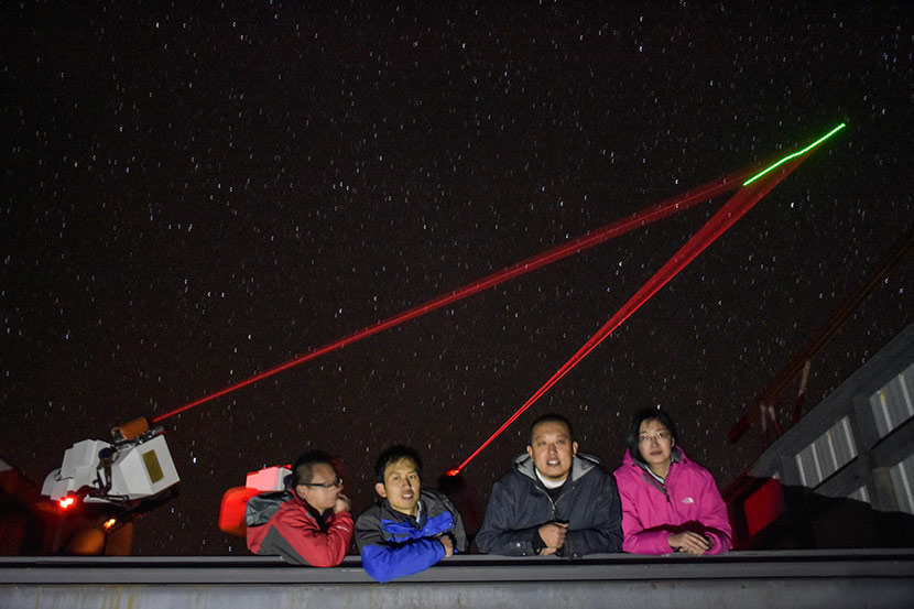 Ren Jigang (second from right) poses for a photo beneath the green trail of the satellite Micius in Ngari Prefecture, Tibet Autonomous Region, Oct. 4, 2014. Courtesy of Ren Jigang