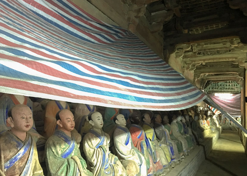 Painted sculptures are covered with a plastic sheeting at Foguang Temple in Wutai County, Shanxi Province, Aug. 28, 2017. From the official weibo of State Administration of Cultural Heritage