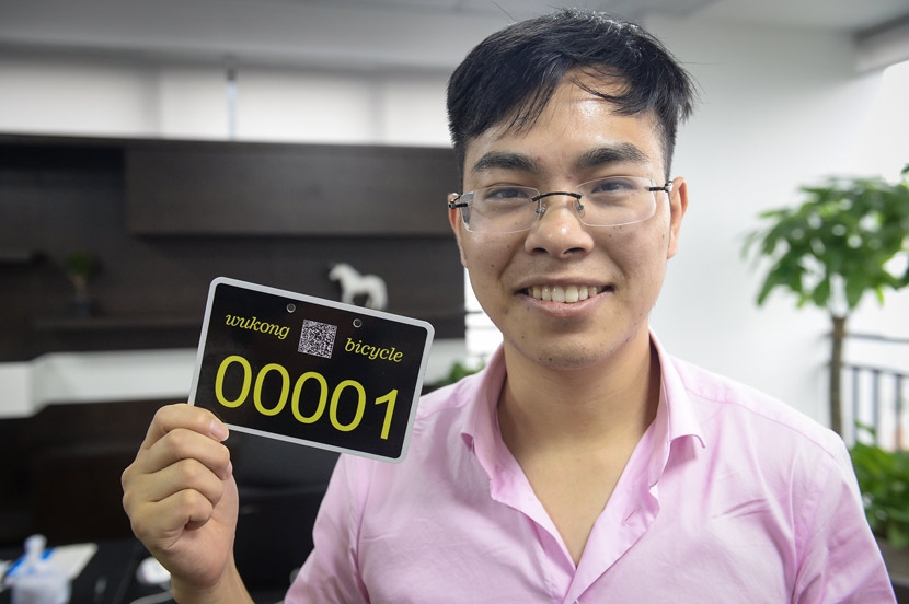 Lei Houyi holds up the first Wukong shared bike license plate at his office in Chongqing, June 19, 2017. Ren Jun/Chongqing Evening News
