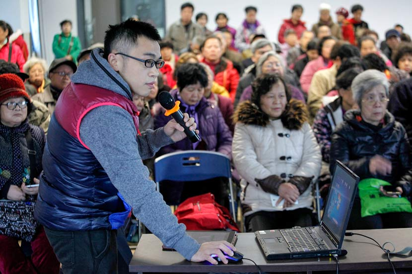 A volunteer demonstrates how to use a mobile phone to an audience of elderly people in Liuzhou, Guangxi Zhuang Autonomous Region, March 6, 2015. Zhang Cunli/VCG