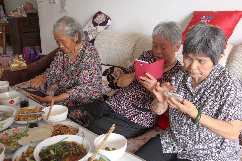 Three elderly women use WeChat to share photos of their lunch in Nanchong, Sichuan province, June 21, 2015. VCG