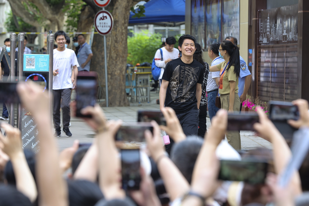 """Family members take photos of """"gaokao"""" candidates as they exit an examination site after completing all components of the test, Xi'an, Shaanxi province, June 8, 2021. IC"""