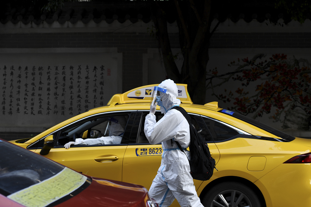 An examinee wearing protective clothing walks out of an examination site in Guangzhou, Guangdong province, June 7, 2021. People Visual