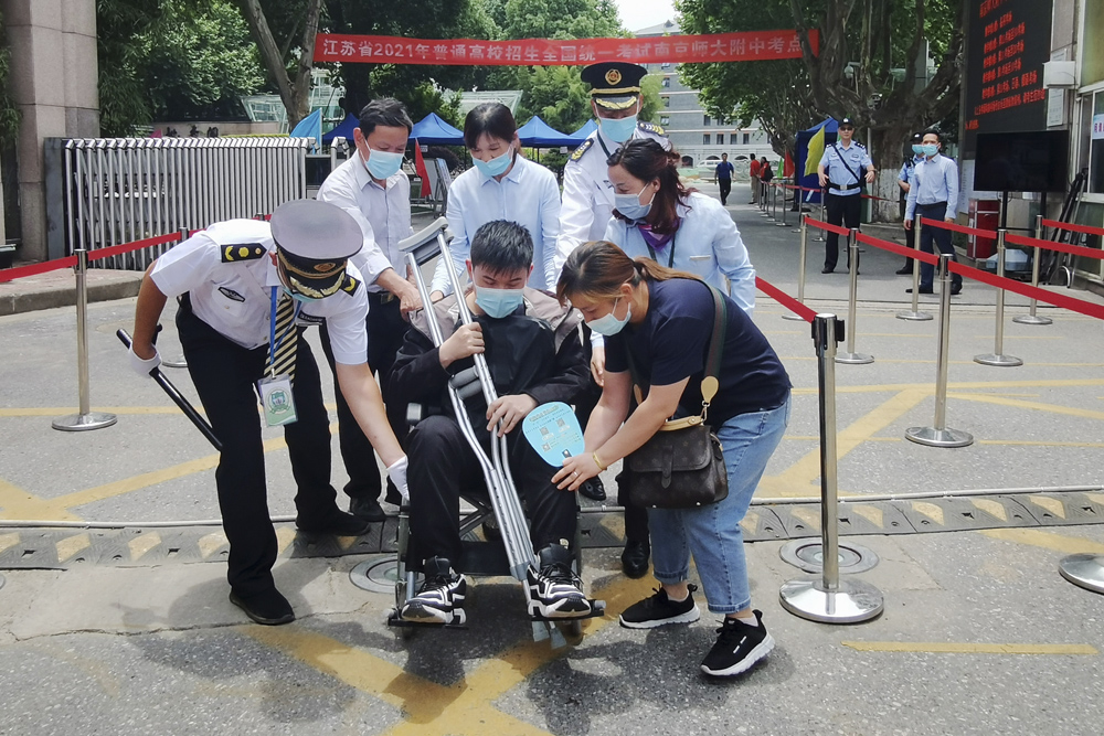 An examinee in a wheelchair leaves a testing facility with the help of site staff in Nanjing, Jiangsu province, June 7, 2021.