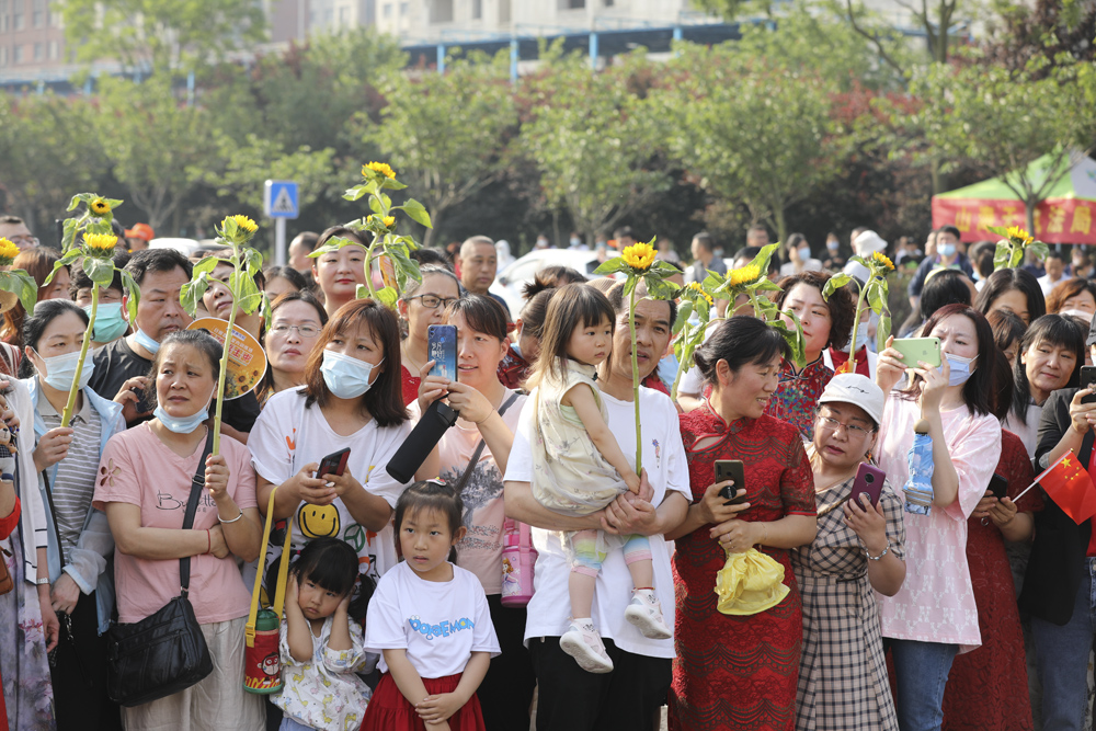 The families of test-takers hold sunflowers for good luck while waiting outside an examination site in Shandong province, June 7, 2021. People Visual