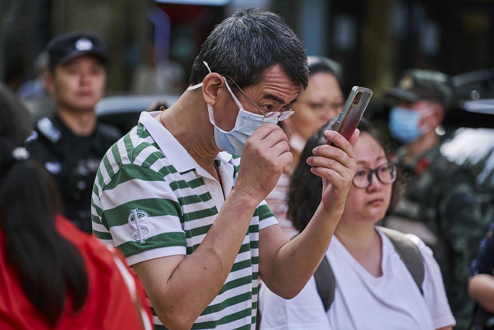 A man checks his cellphone at Xiangming High School in Shanghai, June 7, 2021. Wu Huiyuan/Sixth Tone