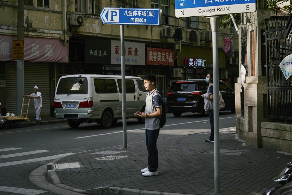 """Gaokao"" candidates stand at a crossroad near Gezhi High School in Shanghai, June 7, 2021. Wu Huiyuan/Sixth Tone"