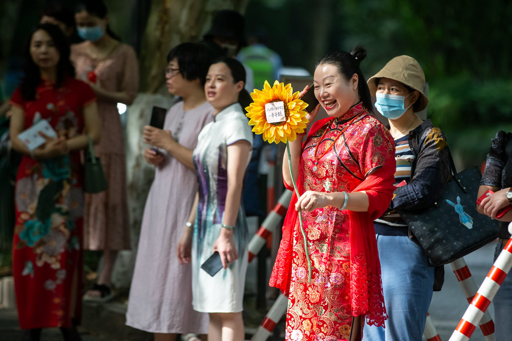 A mother of a test-taker holds a sunflower for good luck while waiting outside an examination site in Hangzhou, Zhejiang province, June 7, 2021. Chen Zhongqiu for Sixth Tone
